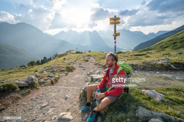 wanderer-männlich ruht auf trail in der schönen natur in den schweizer alpen - kanton graubünden stock-fotos und bilder