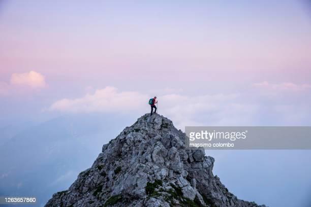 hiker man on the top of mountain during twilight - montañismo fotografías e imágenes de stock