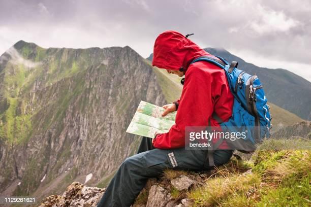 wanderer mensch liest karte auf berggipfel - siebenbürgen stock-fotos und bilder