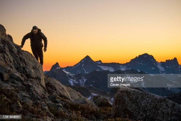 hiker navigates a mountain route using headlamp after sunset. - approaching stock pictures, royalty-free photos & images