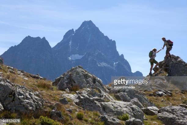 hiker offers hand to companion, on mountain ridge, piedmont, italy - scalare foto e immagini stock