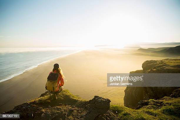 A hiker on a cliff watching sunset
