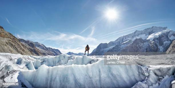 Hiker on a glacier looking out at view, Aletsch Glacier, Switzerland