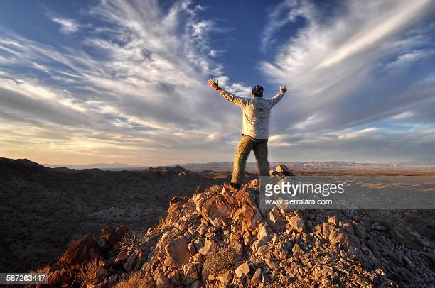 hiker on a mountain summit with clouds - lake havasu stock photos and pictures