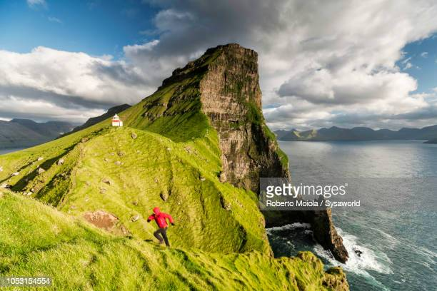 hiker on cliffs, kallur lighthouse, faroe islands - islas faroe fotografías e imágenes de stock