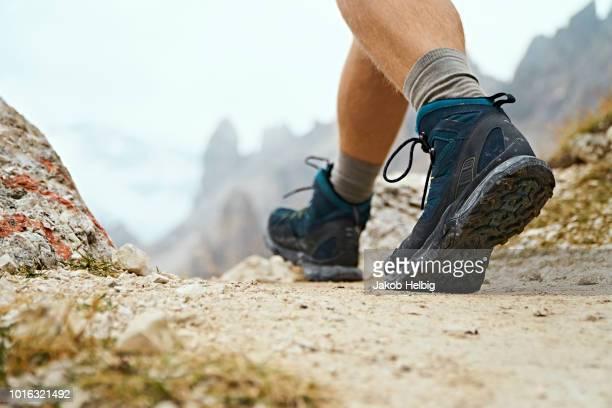hiker on dirt track, canazei, trentino-alto adige, italy - laars stockfoto's en -beelden