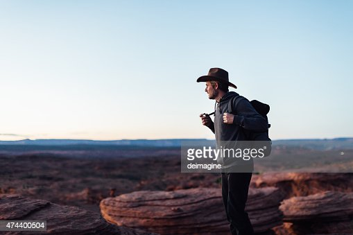 Hiker on edge of Grand Canyon cliff in Arizona