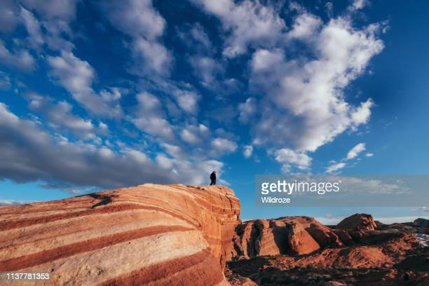 hiker on fire wave trail rock formations, hiking in valley of fire state park - nevada stock pictures, royalty-free photos & images