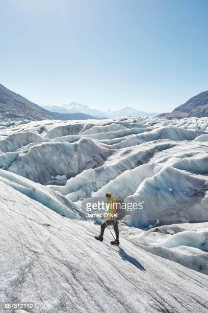 Hiker on glacier looking out at distant mountains, Aletsch Glacier, Switzerland
