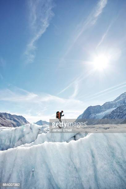 Hiker on glacier with distant mountains, Aletsch Glacier, Switzerland
