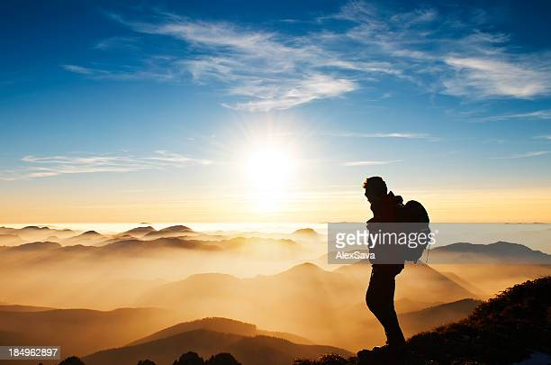 Hiker on mountain at sunset