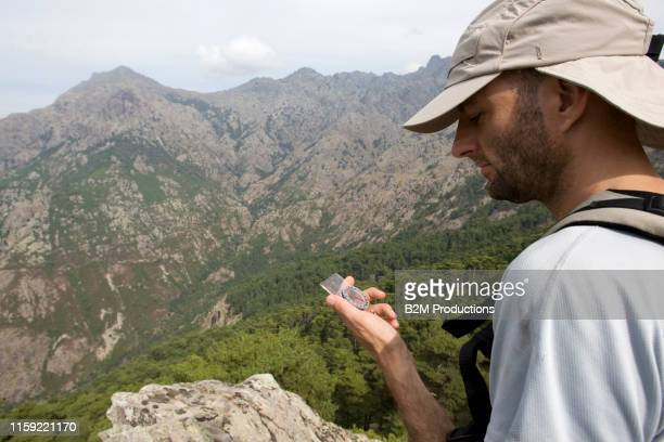 hiker on mountain checking for directions - 2010 2019 stock pictures, royalty-free photos & images