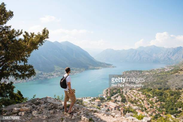 Hiker on mountain looking away at elevated view of sea, Kotor, Montenegro, Europe