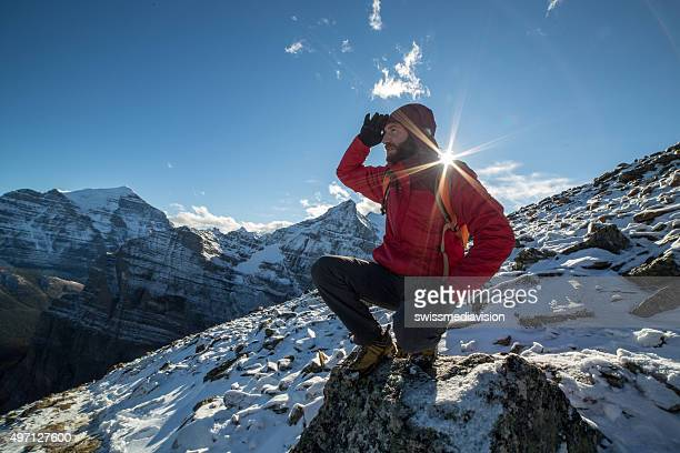 Hiker on mountain top looks at spectacular mountain scenery