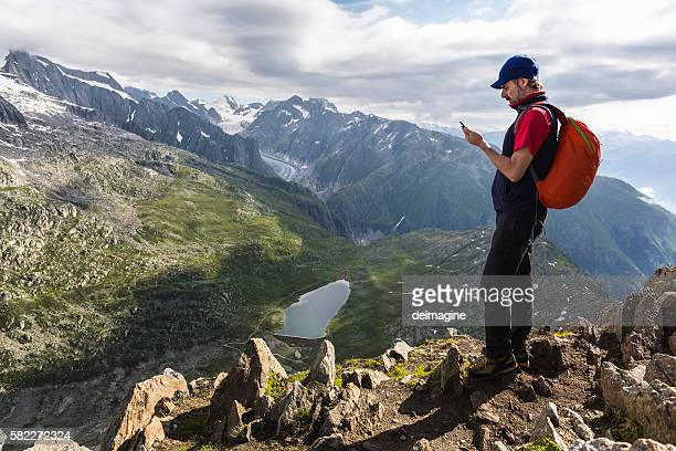 Hiker on mountains checks his smartphone
