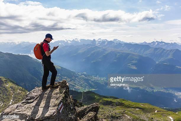 Hiker on mountains checks his smartphone