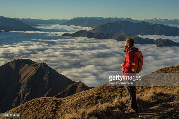 Hiker on moutain top contemplates view