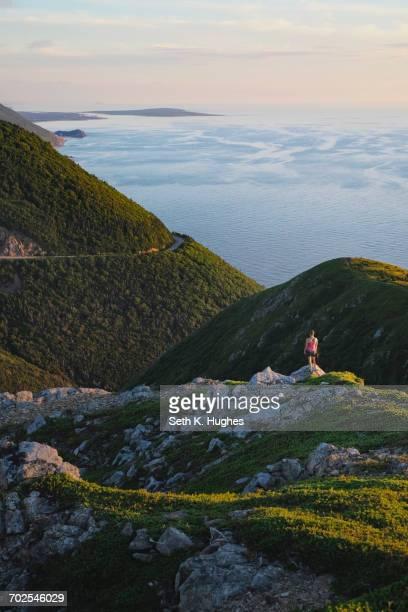 hiker on rocky outcrop, cape breton, nova scotia, canada - cape breton island stock pictures, royalty-free photos & images