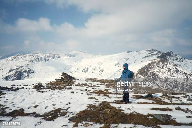 Hiker on snow-covered mountain, Coniston, Cumbria, United Kingdom
