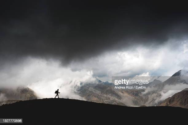 hiker on the gran sasso, abruzzo, immersed in the clouds. - andrea rizzi photos et images de collection