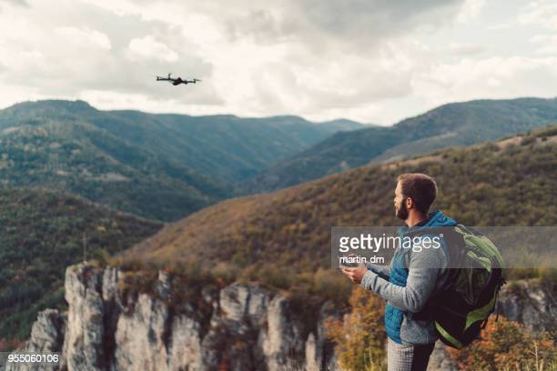 hiker on the mountain top flying a drone to make videos and photos - flying stock photos and pictures
