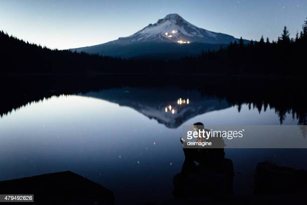 Hiker on the shore of the lake during twilight