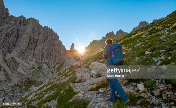 hiker on their ascent to the hochvogel, fuchskarspitze in the background, balkenspitzen, sonnenstrahlen am morgen, allgaeu, allgaeuer hochalpen, bavaria, germany - morgen stock pictures, royalty-free photos & images