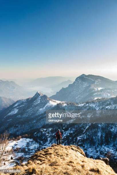wanderer auf dem gipfel des berges mit blick auf das panorama - hoch position stock-fotos und bilder