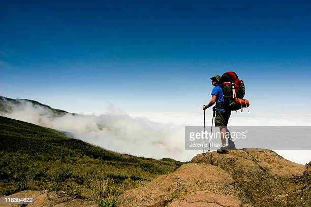 hiker overlooking mount kilimanjaro on the way up to the summit. - kilimanjaro stock photos and pictures