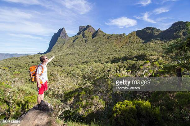 Hiker overlooking the rainforest and pointing at the caldera of Cirque de Mafate, Reunion island