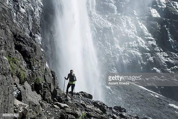 Hiker pauses below waterfall to admire view