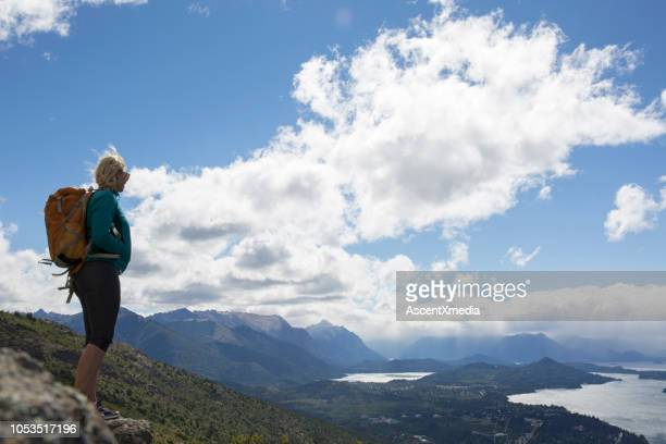 Hiker pauses on bluff above lakes and mountains