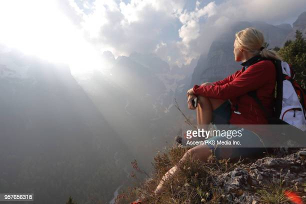 Hiker pauses on cliff edge, looks towards mountains