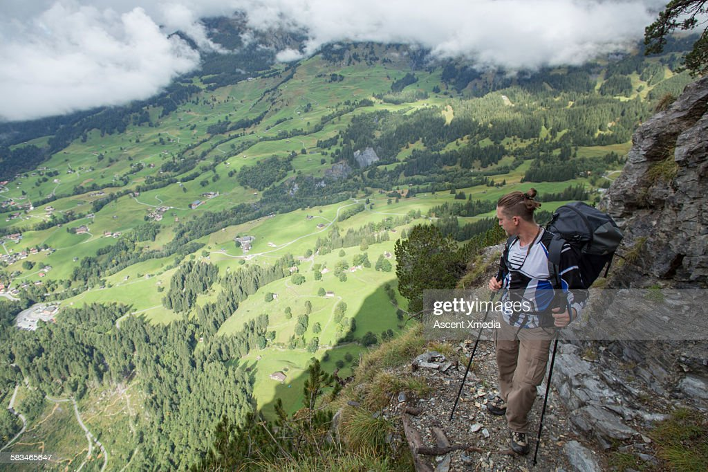 Hiker pauses on mountainside, looks down to valley : Stock Photo