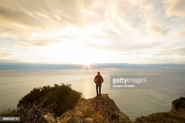 Hiker pauses on ridge above sea, looks towards sun