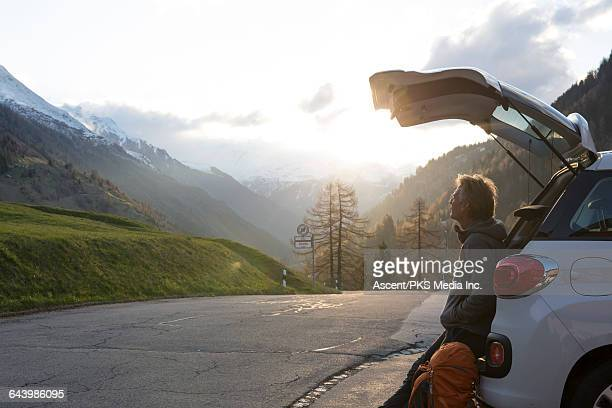 hiker pauses to watch sunrise on mountain road - hands in pockets stock pictures, royalty-free photos & images