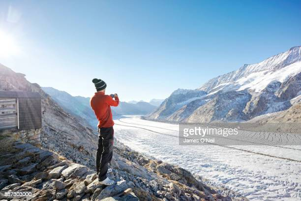 Hiker photographing glacier and mountains with phone, Aletsch Glacier, Switzerland
