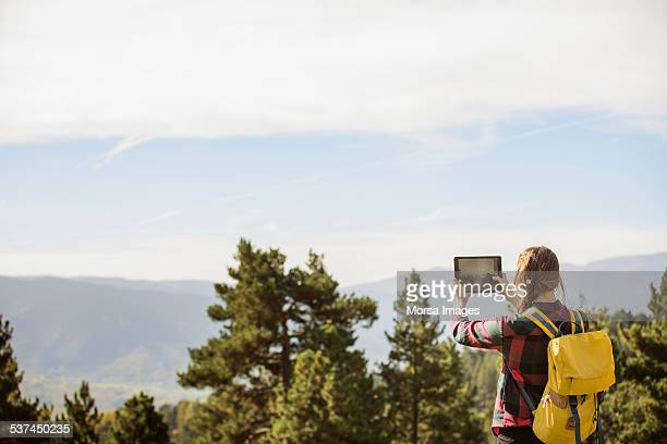 Hiker photographing scenery through digital tablet