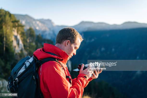 hiker photographs mountain valley at sunrise - red jacket stock pictures, royalty-free photos & images