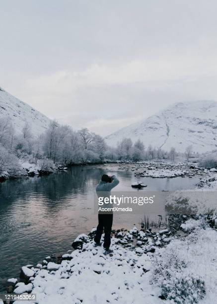 hiker photographs snowy lake and rugged landscape - winter stock pictures, royalty-free photos & images