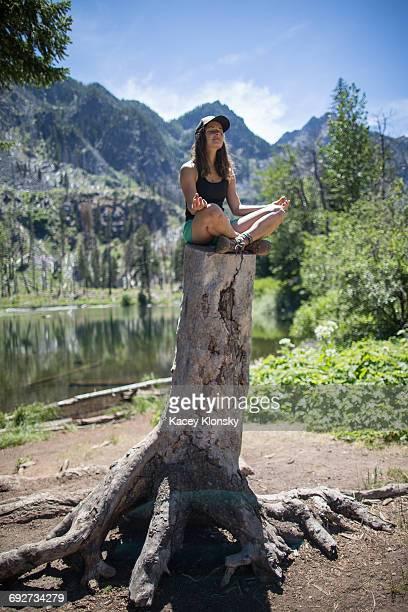 Hiker practising yoga on tree stump, Enchantments, Alpine Lakes Wilderness, Washington, USA