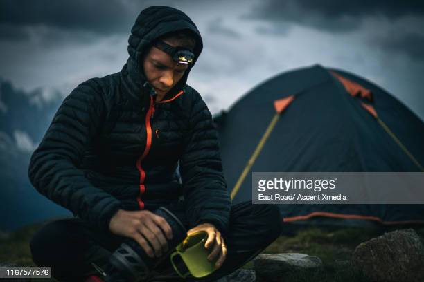 hiker prepares dinner beside tent, in high alpine meadow - padded jacket stock pictures, royalty-free photos & images
