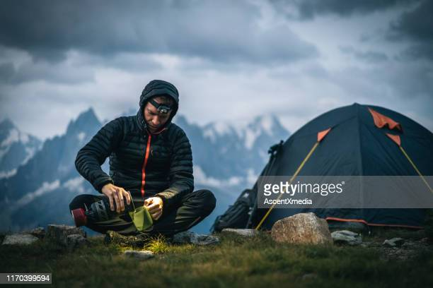 hiker prepares hot beverage with headlamp in alpine campsite - focus on background stock pictures, royalty-free photos & images