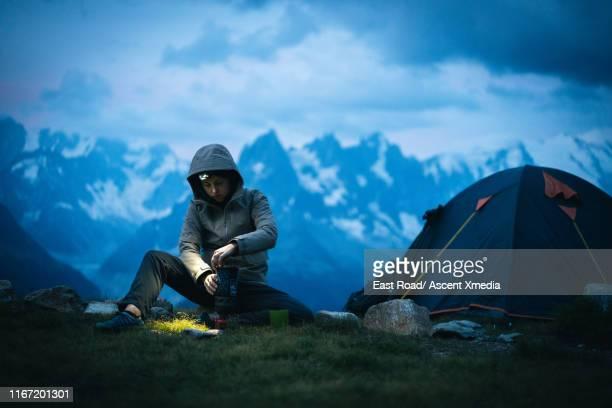 hiker prepares meal in mountain landscape, at dusk - キャンプ 1人 ストックフォトと画像