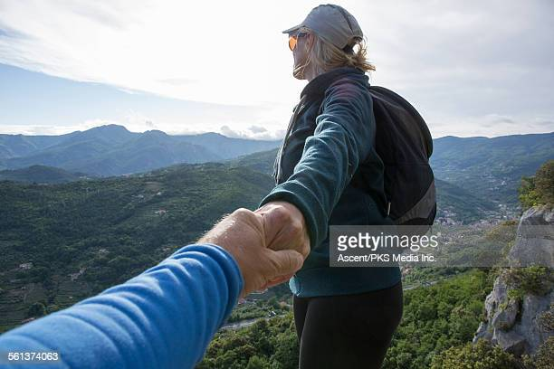 hiker provides assistance to companion, cliff edge - persoonlijk perspectief stockfoto's en -beelden