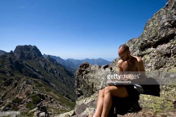hiker reading guide on mountain in corsica - 2010 2019 stock pictures, royalty-free photos & images