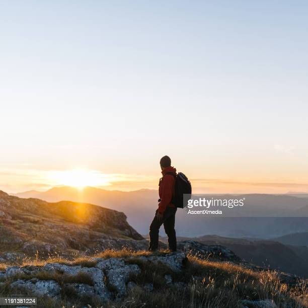 hiker relaxes above mountain valley at sunrise - sunrise contemplation stock pictures, royalty-free photos & images