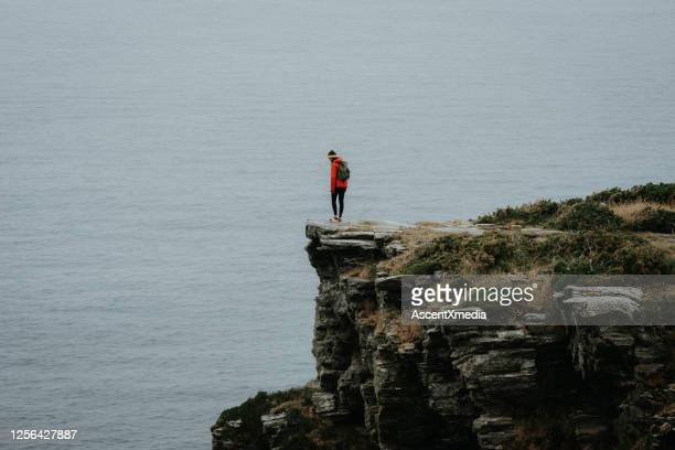 hiker relaxes on coastal mountain cliff - cliff stock pictures, royalty-free photos & images