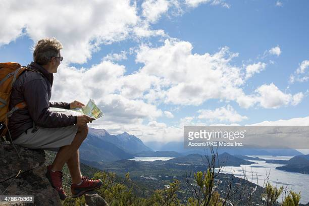 Hiker relaxes on mountain promontory, consults map