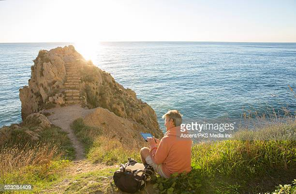 Hiker relaxes on slope above sea, w digital tablet